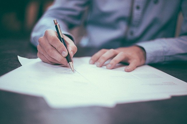 Osoba pisząca długopisem na kartce - ochrona sygnalistów