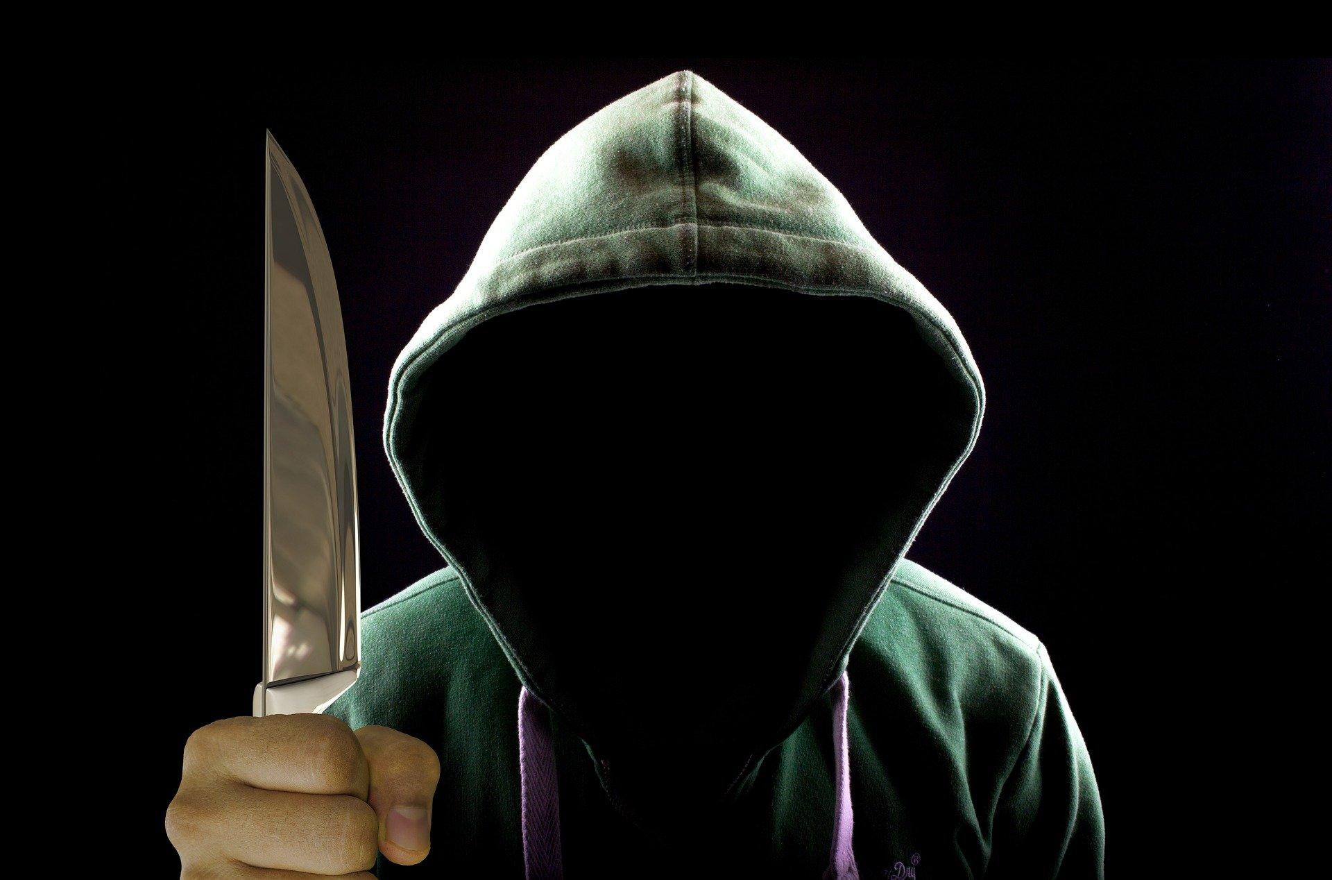 Postać w kapturze trzymająca nóż - atak na urząd